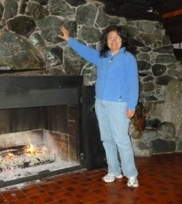 poet Muriel standing by fireplace gensturing up